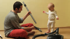 Father show to his little baby how to assemble vacuum cleaner Stock Footage