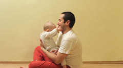 Baby sitting on his father lap, playing with his face, father bite his finger Stock Footage
