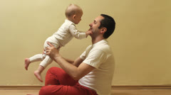 Young father rise up hit sweet baby, playing indoor Stock Footage