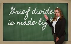 teacher showing grief divided is made lighter on blackboard - stock photo