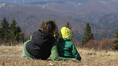 Baby and his mother resting on mountain pateau and watch the mountain view Stock Footage