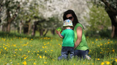Lovely child and mother in blossom orchard, baby run and hold a hand mill toy Stock Footage