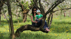 Mother resting on branch of blossom tree take of the baby shoes and socks  Stock Footage