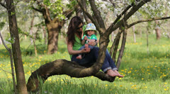 Young mother and cute baby sitting on blossom branch, mother tickle his son sole Stock Footage