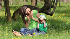 Young mother clapping her hands, baby arrange his sunglass, together in meadow - stock footage