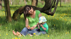 Funny baby and his mother in green meadow, baby arranging sun glasses - stock footage