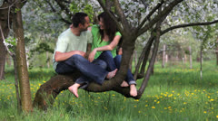 Couple having fun together, resting on blossom branch tree Stock Footage