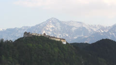 Old citadel up on the mountains, green conifer mountains and snowed mountains Stock Footage