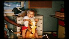 Black maid rocks the baby on rocking horse, 83 vintage film home movie Stock Footage