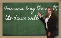 Teacher showing however long the night, the dawn will  break on blackboard Stock Photos