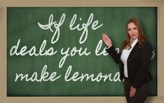 Teacher showing if life deals you lemons, make lemonade on blackboard Stock Photos