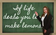 Stock Photo of teacher showing if life deals you lemons, make lemonade on blackboard