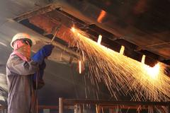 A welder working a torch at shipyard Stock Photos