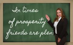 Teacher showing in times of prosperity friends are plentiful on blackboard Stock Photos