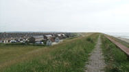 Stock Video Footage of Village behind seawall + pan Hondsbossche Zeewering