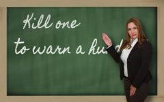 teacher showing kill one to warn a hundred on blackboard - stock photo