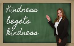teacher showing kindness begets kindness on blackboard - stock photo