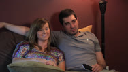 Stock Video Footage of Young couple MF mid 20's laughing, watching TV