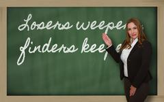 Teacher showing losers weepers, finders keepers on blackboard Stock Photos