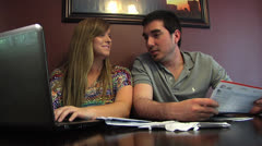 People, Young couple mid 20's 2shot happy exchanges,  paying monthly paper bills Stock Footage