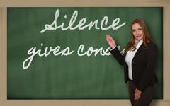 teacher showing silence gives consent on blackboard - stock photo