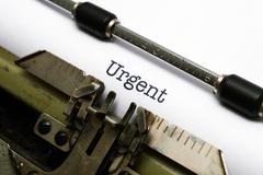 Urgent text on typewriter Stock Photos