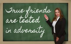 Teacher showing true friends are tested in adversity on blackboard Stock Photos