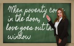 Stock Photo of teacher showing when poverty come in the door, love goes out the on blackboar