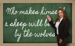 teacher showing who makes himself a sheep will be eaten by the wolves on blac - stock photo