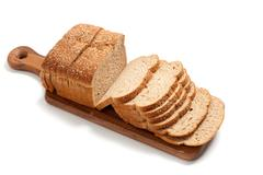 loaf of whole grain bread on a board - stock photo