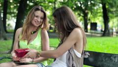 Woman giving birthday gift to her friend in city park HD Stock Footage