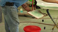 Male technician puts mud on a door panel to begin bodywork Stock Footage