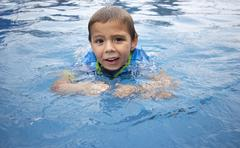 Boy with surprised look in swimming pool - stock photo