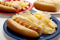 Several hotdogs on colored plates Stock Photos
