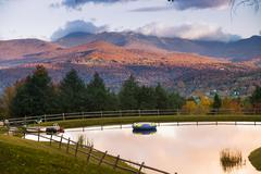 swimming pond with mt. mansfield in the autumn. - stock photo