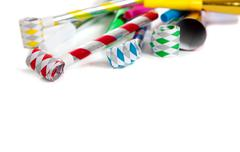 assorted noise makers on white with copy space - stock photo