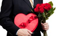Man holding roses and red heart with chocolates on white Stock Photos