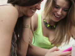 Stock Video Footage of Young happy girlfriends with smartphone in cafe NTSC