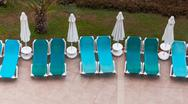 Stock Photo of empty sun loungers by the pool