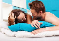 Young couple having fun in a bed Stock Photos