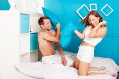 young couple having fun making pillows fight. - stock photo