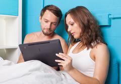 young couple browsing internet on tablet computer while sitting in bed - stock photo