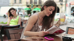Beautiful woman reading magazine in cafe, steadicam shot HD Stock Footage