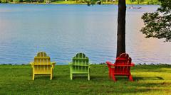 Colorful chairs at lake fishermen backgroun - stock photo