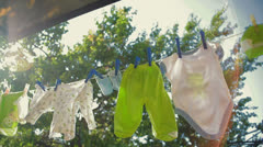 baby clothes hanging on a rope and drying - stock footage
