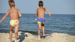 Two boys run up and jump into the sea Stock Footage
