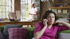 Attractive young woman talking on her cell phone at home Stock Footage