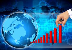 hand pulling up a bar from a graph  on abstract the world business - stock photo