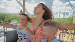 Mom with two kids ride on the Ferris wheel Stock Footage