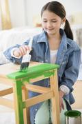Mixed race girl painting stool Stock Photos